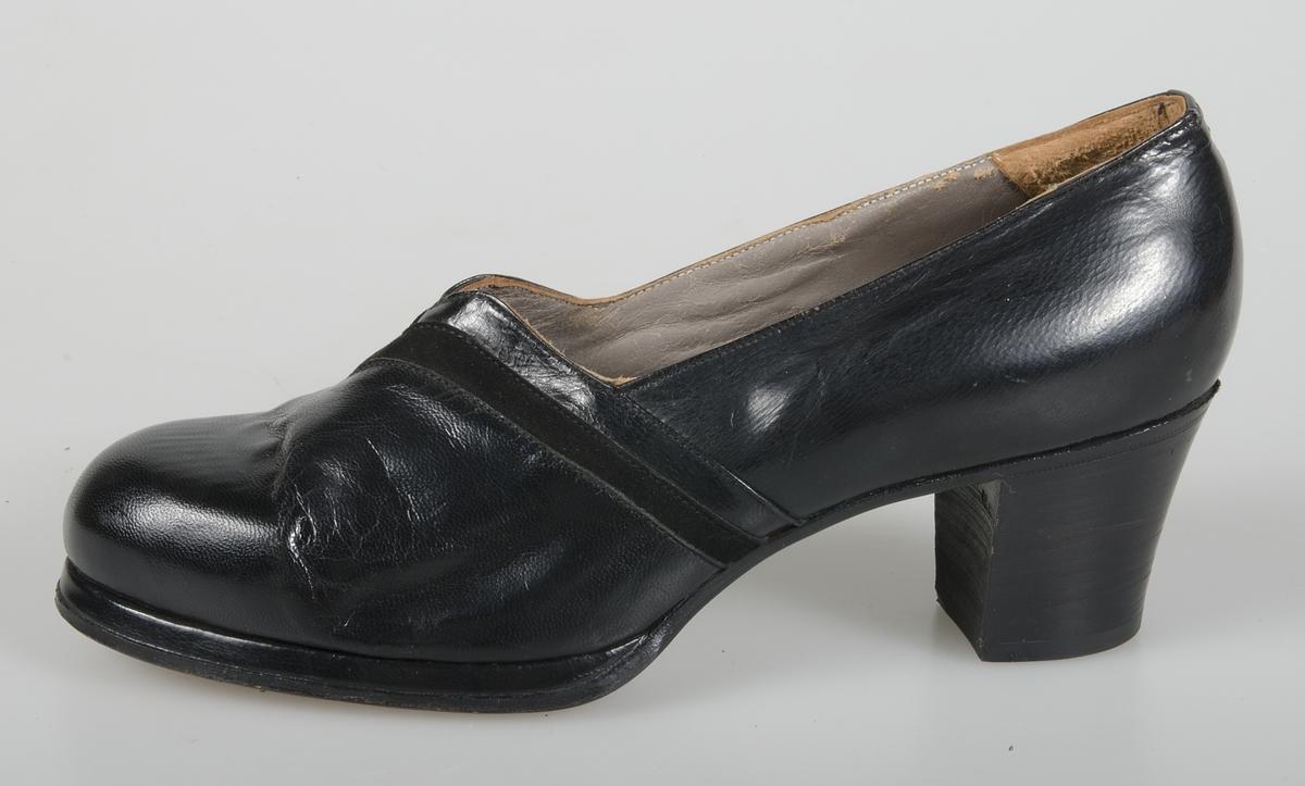 Damsko av svart skinn, pumpsmodell med 5,5 cm hög klack med gummibeläggning. Lädersula  märkt: AB I E L o Co, P - licens 680. Årtalet 1942 skrivet under skon. Storlek 5 A.