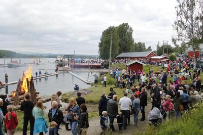 Foto av sankthansbål på elvebredd og mange mennesker rundt.