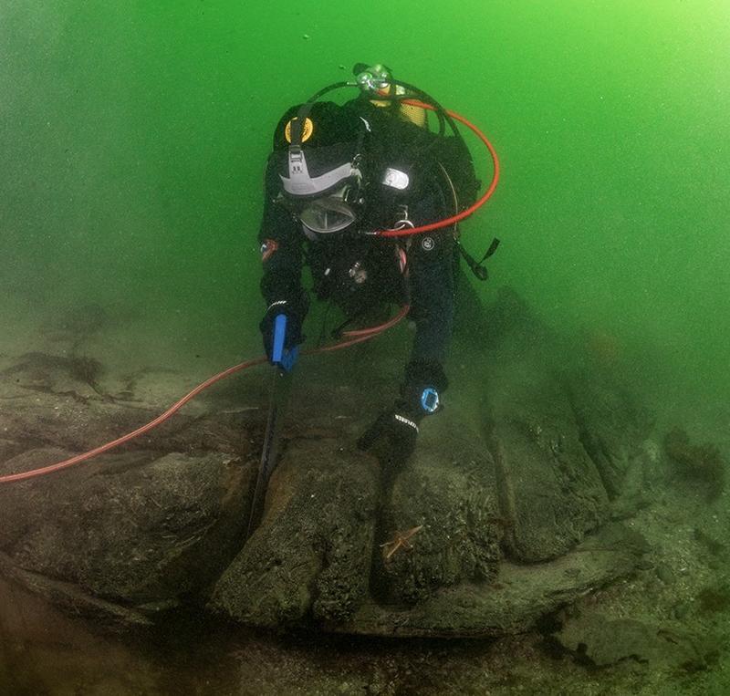 Dykker under vann sager i vrak på sjøbunnen: Arkeolog Elling Utvik Wammer sager ut skiver av hudbord til datering av skipsvraket ved Drengeholmen. (Foto/Photo)