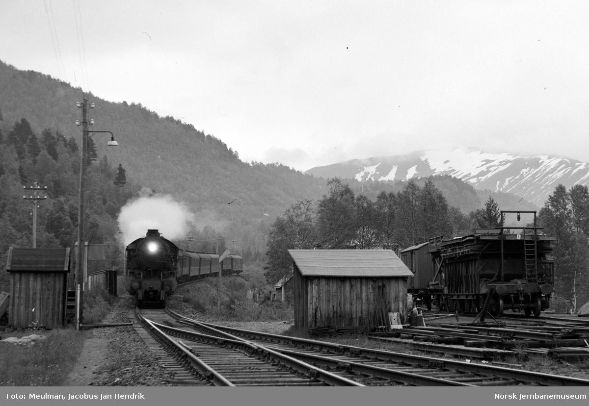 Damplokomotiv type 31b med nattoget fra Oslo Ø til Bergen, tog 605, kjører inn på Reimegrend stasjon.