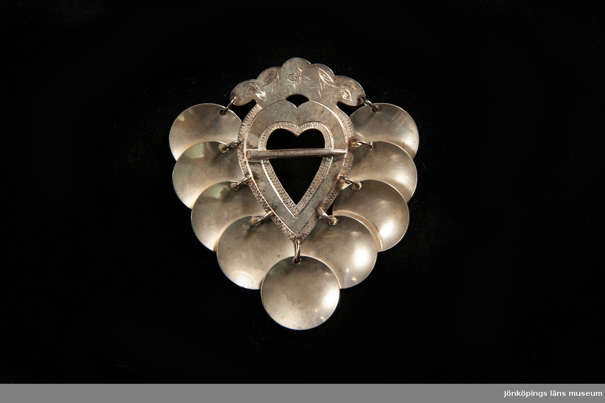 """En hjärtformad bröstsölja av silver med stiliserad krona överst, prydd med graverad blomdekor. Behängd med 9 runda silverplattor (""""skålar"""")."""