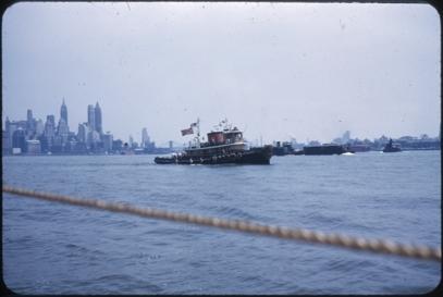 Slepebåt med norsk og amerikansk flagg. Skoleskipsgutter ombord. I bakgrunnen sees Manhattan skyline og Brooklyn. Bildet er tatt fra et annet skip.