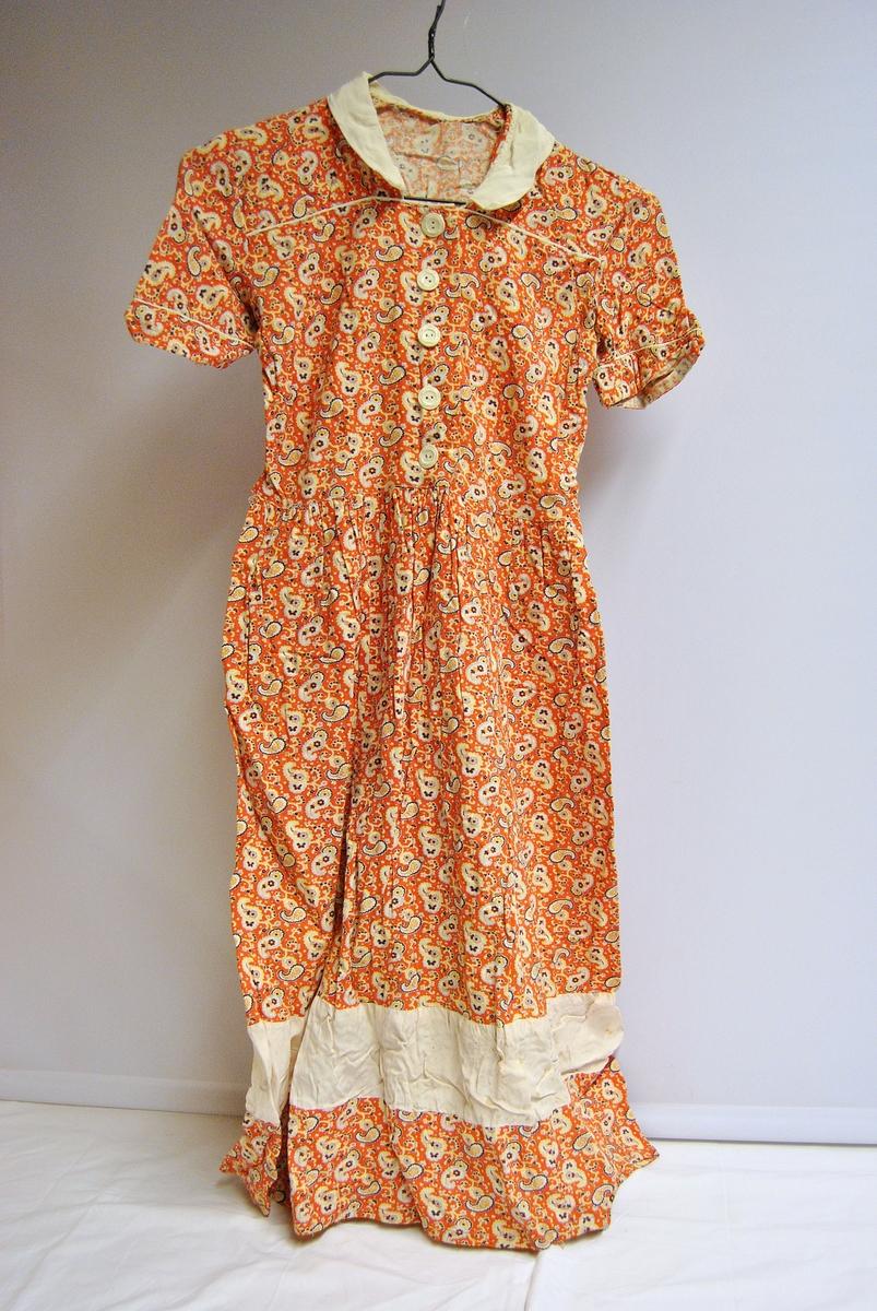 Heimesydd kjole. Knapper i bysten. A-forma skjørt. Paisley-mønstra. Kvit krage og kvitt felt i skjørtet. Ermene har t-skjorte-lengde, med påsydd oppbrett.