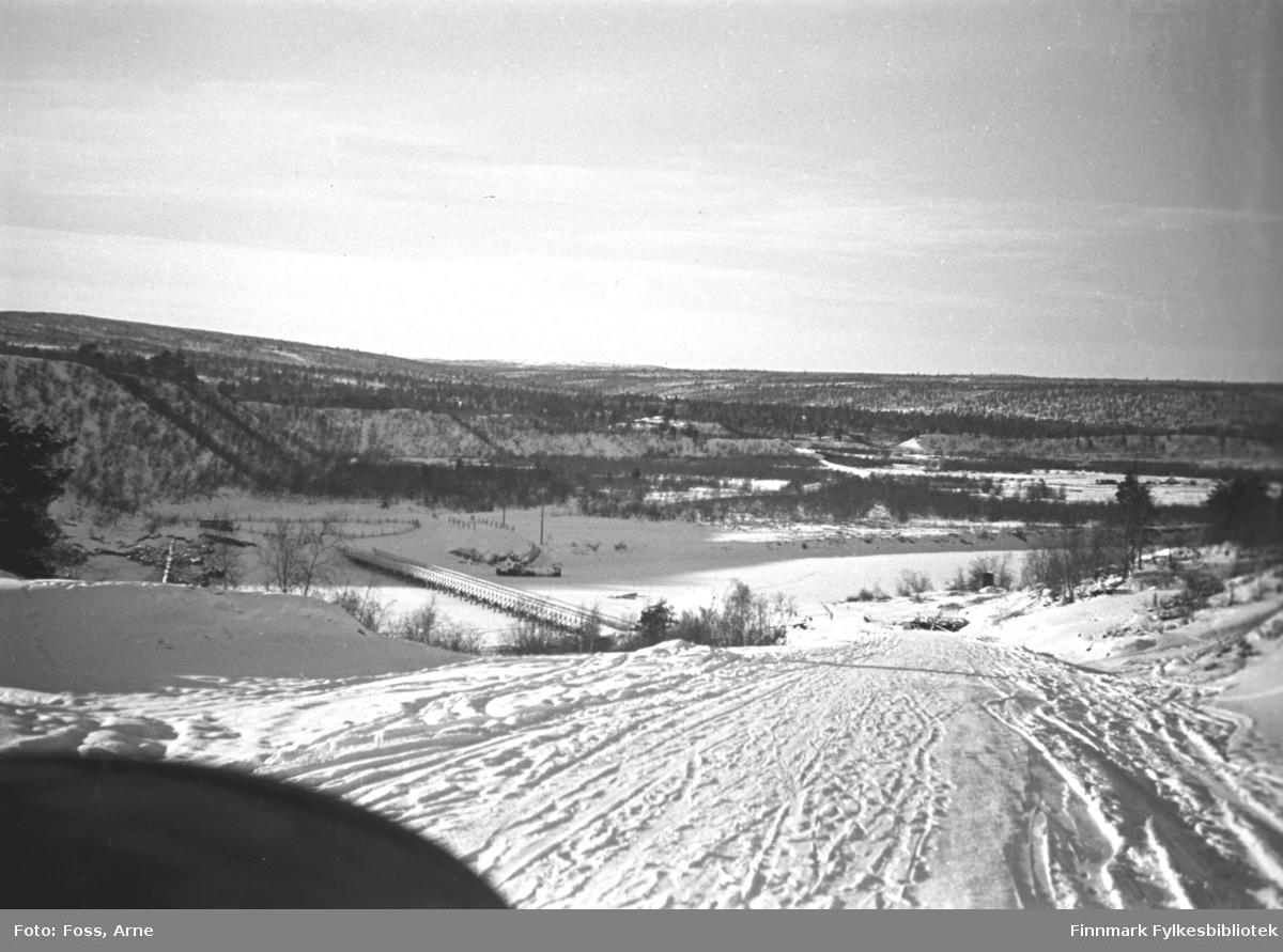 Bilen kjører langs veien i Karigasniemi ved grensen til Norge (i Utsjok kommune i Finland) mot brua og Karasjok kommune, februar-mars 1947. Anarjohka er en grenselv mellom Finland og Norge.