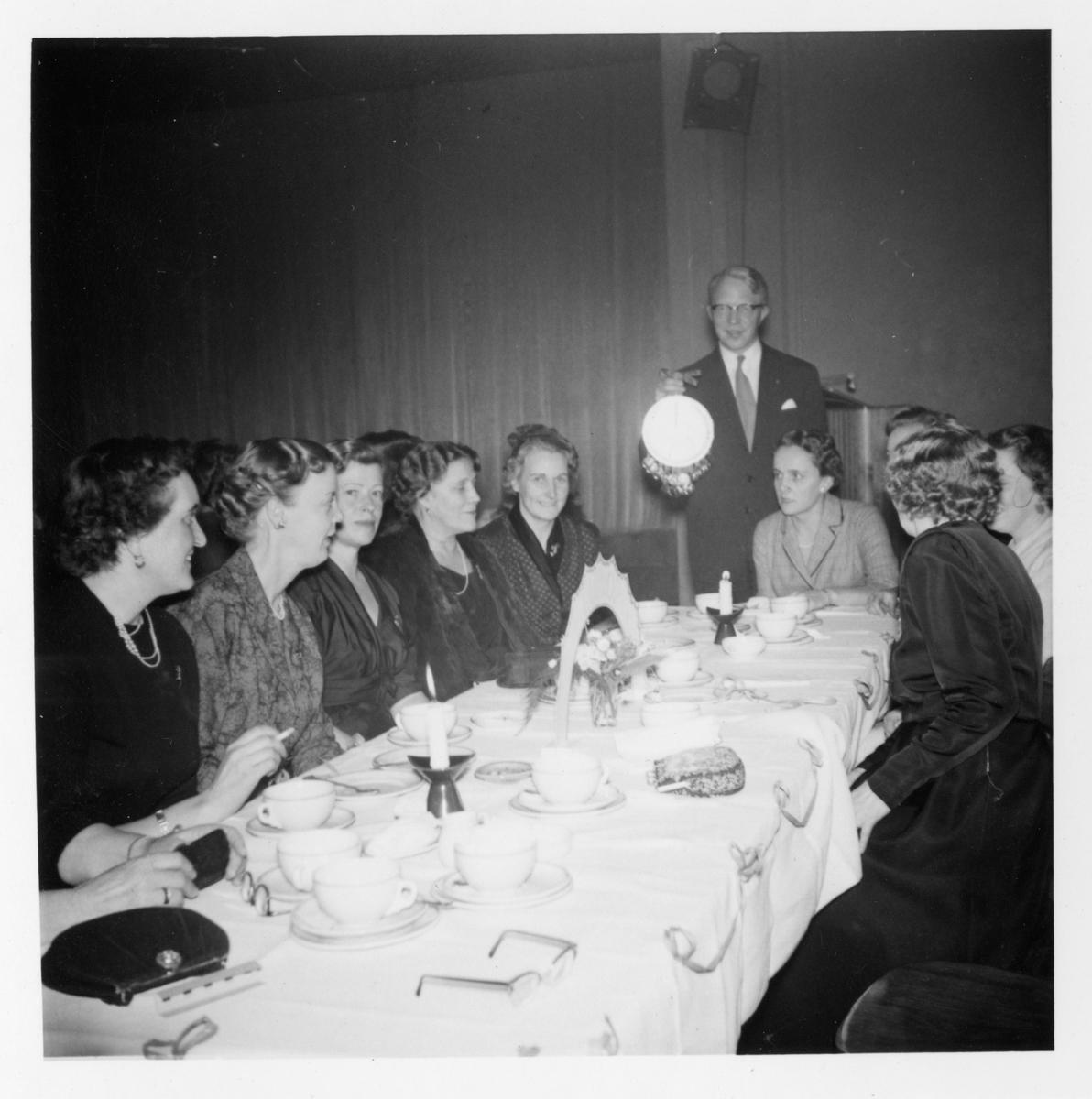 Deltagare sitter vid ett dukat kaffebord under ett möte med Fredrika-Bremer Förbundet 1957.