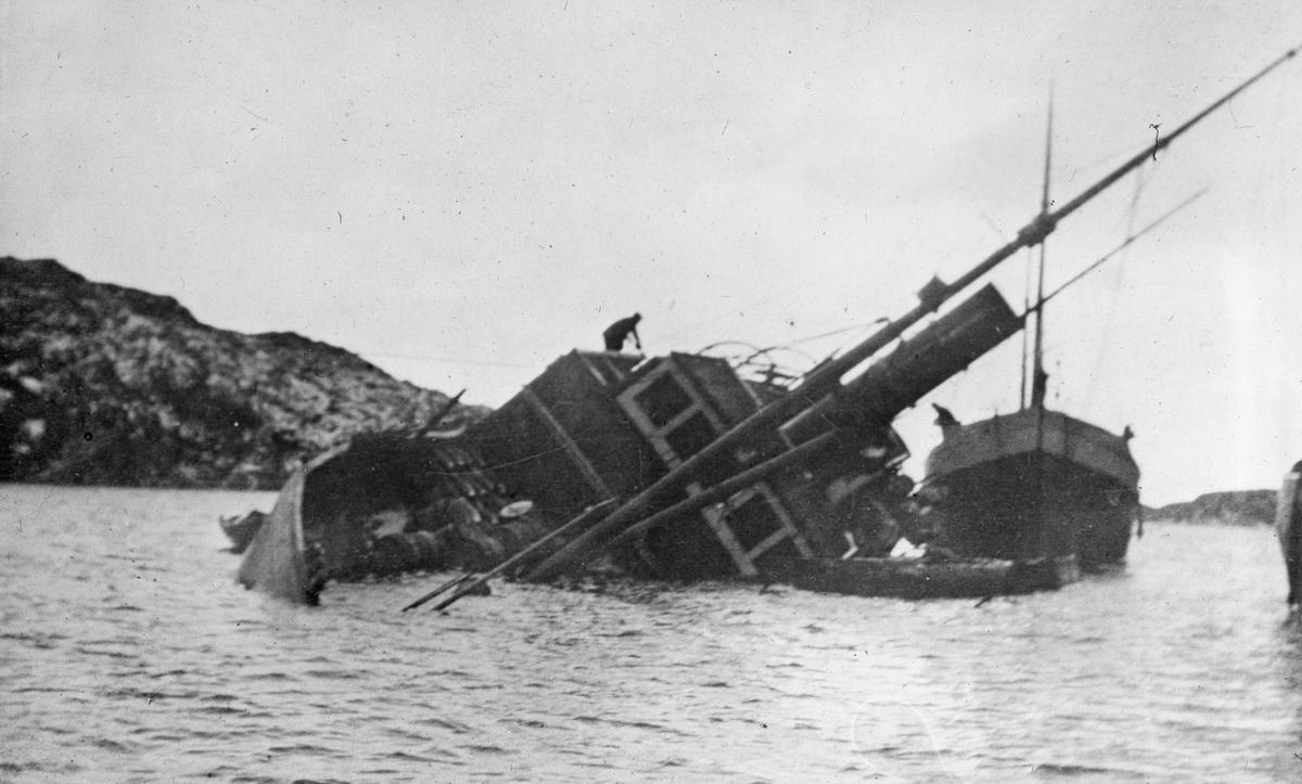 Dampskip med slagside. En mann står oppe på skipets langside. Et fartøy ligger fortøyd bak havaristen.