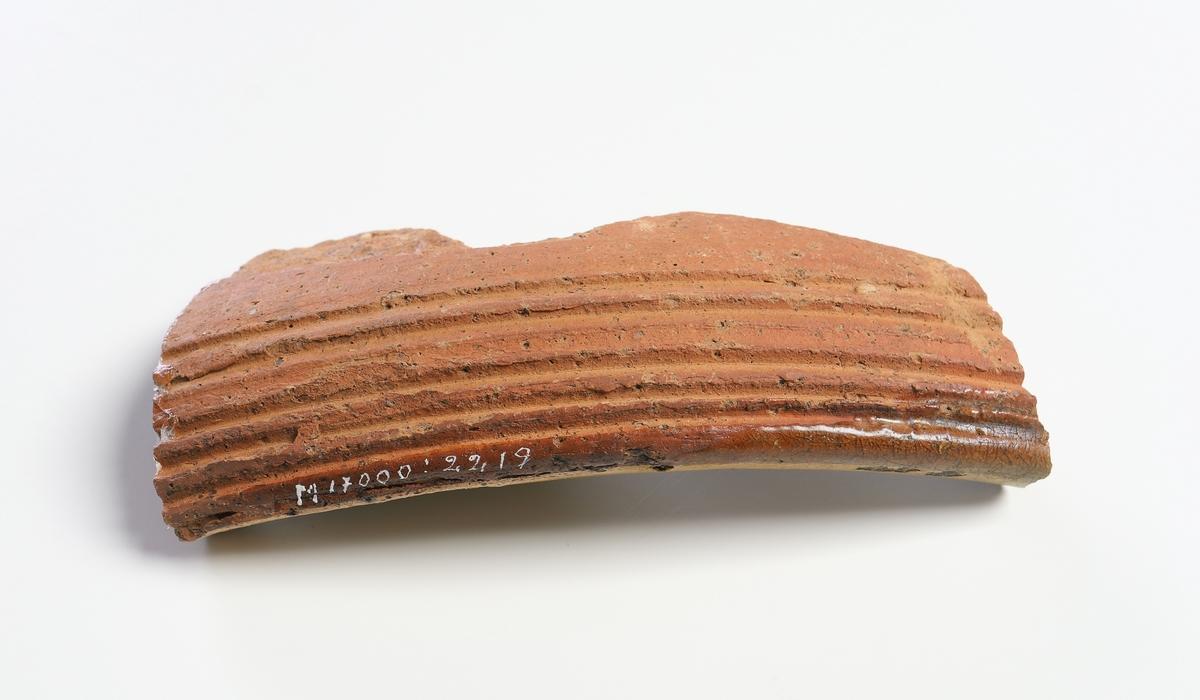 Del av mynningskant av yngre rödgods med brun glasyr på insidan. Dekor med vit piplera och grön glasyr. Utsida med tydliga drejfåror vid mynningsranden.
