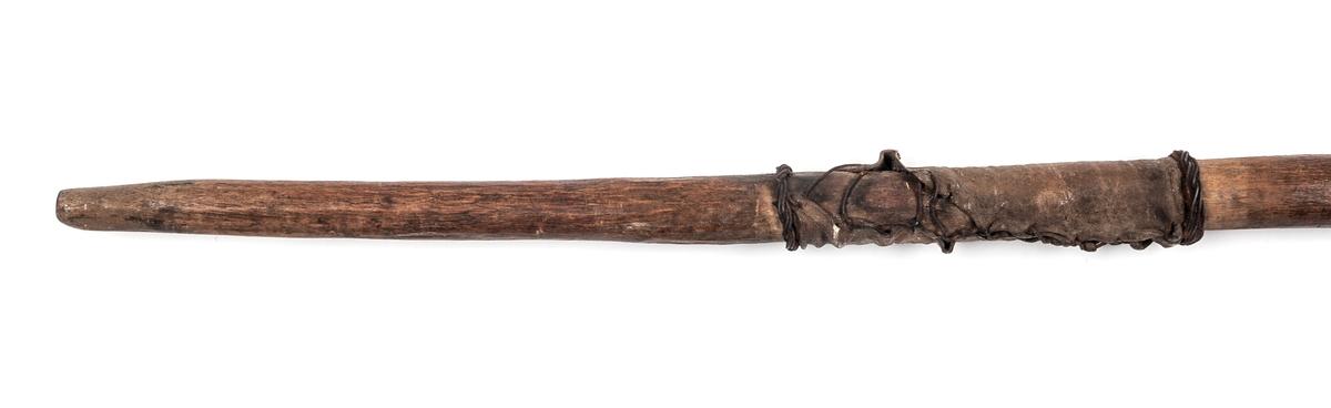 Spjut, med kort dubbeleggat järn med lång tånge. Själva eggjärnet 8cm. Total längd 1,40m. Skaft av trä, delvis skinnklätt. Afrika.