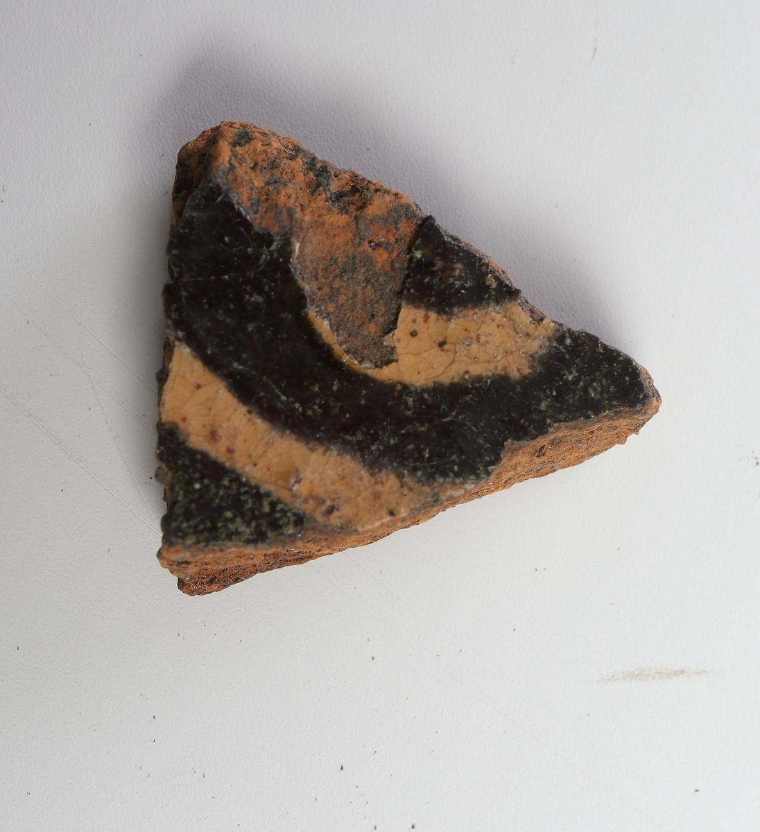 Buk-/bottenfragment av yngre rödgods. Mörkbrun glasyr med två ränder av vit piplera på skärvans insida. Slät utsida.