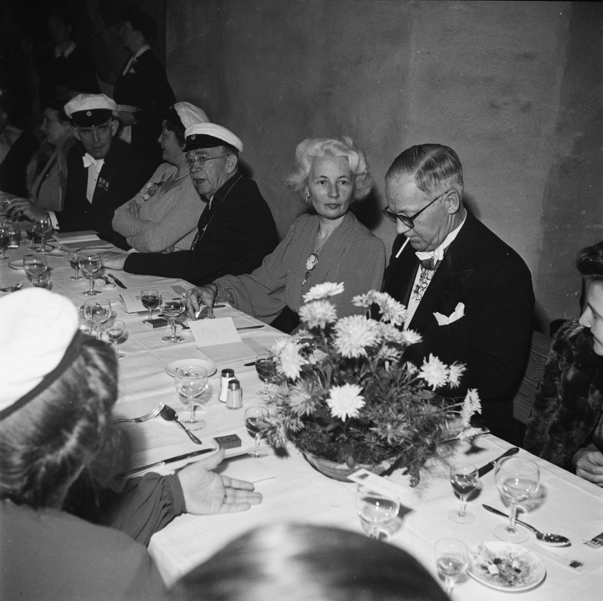 Män och kvinnor i studentmössor vid dukat festbord, sannolikt på rikssalsbanketten i samband med Östgöta nations 300-årsjubileum, Uppsala 1946