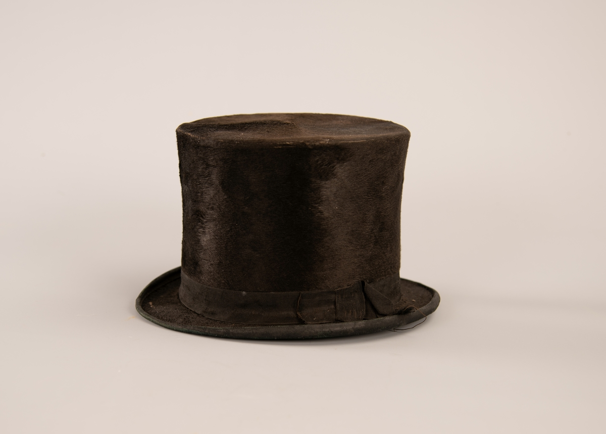 Svart flosshatt med svart ripssilkebånd som kanter bremmen. Ripssilkebåndet er festet som en sløyfe på siden. Oval, sylindrisk pull som er flat på toppen. Bremmen er hovedsakelig flat, med en liten bøy på sidekantene. Svettebånd av skinn. Innsiden er oppstivet med papp.  Om kastorhatt: Kastorhatt (også skrevet castorhatt), beverhatt eller hårhatt var en type mannshatt som var laget av eller trukket med kastor,[1] det vil si en type filt, opprinnelig laget av beverhår, seinere også imitasjoner fra kanin og bløte, vevde stoffer som langhåret fløyel, felpel og plysj. Kastorhatter kom i bruk allerede 1550, men var særlig vanlige fra rundt 1750 til 1850. Den sammenpressede hårfilten var slitesterk, lett å forme og kunne børstes slik at materialet fikk en egen glans. Mange av de tidlige flosshattene var av kastorstoff. Andre stoffer har siden overtatt, blant annet silke.   Det ble slaktet millioner av bevere for å skaffe skinn til hårhattene. Da silke overtok som materiale i herrehattene på begynnelsen av 1800-tallet, kan det ha reddet beveren fra utryddelse.  Kilde: https://no.wikipedia.org/wiki/Kastorhatt (oppsøkt 09.10.2018)