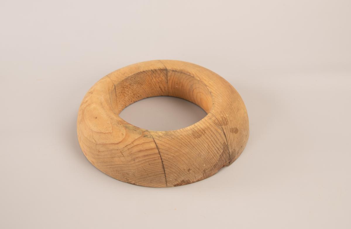 Oval hatteblokk med hull i midten. De ytre kantene av blokken er avrundet ned mot en flat bunn. En kvist har løsnet fra treeverket på undersiden.