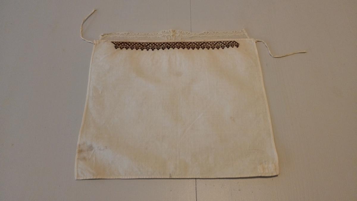 1 hylk.  Hyllik av hvitt lerred, 28 x 24 cm. Har foran en bord sortsöm og er kantet med en knipling.  Kjöpt av Anna O. Burgum?, Framfjorden.