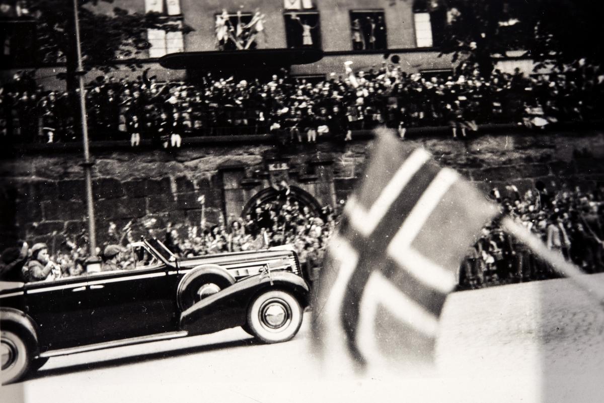 Kronprinsen vinker fra bilen i paraden på vei opp Karl Johans gate i Oslo våren 1945.