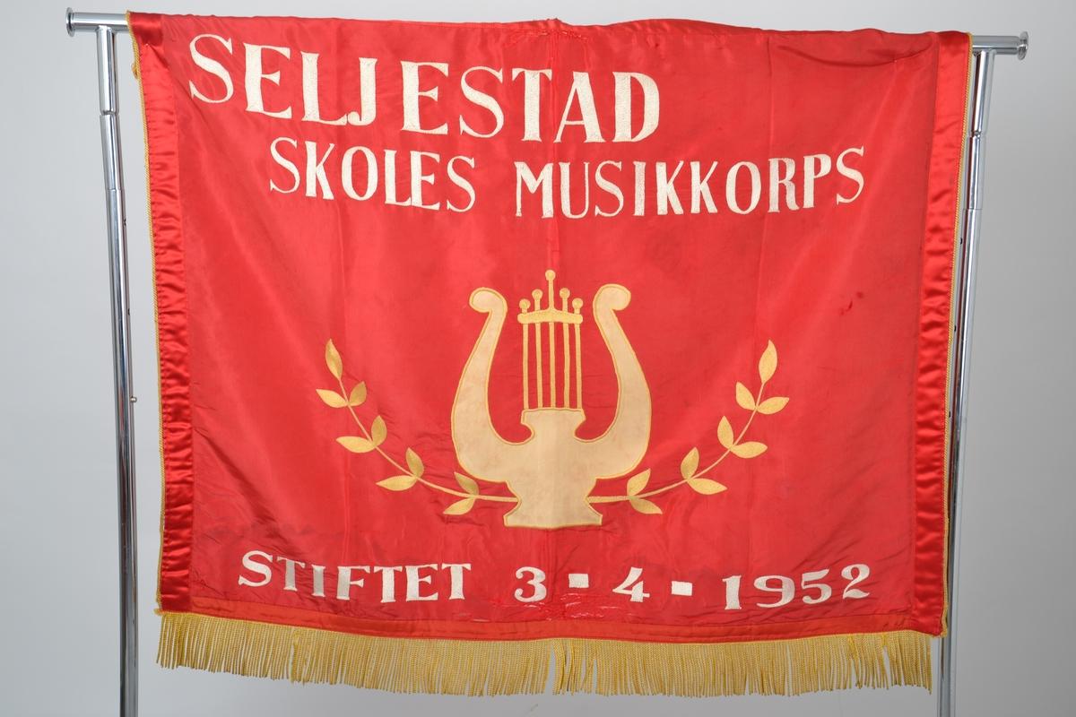Fane i rød silke med gullsnorer og brodert dekor og skrift med hvit og gul tråd. Noe skader og reparasjoner.