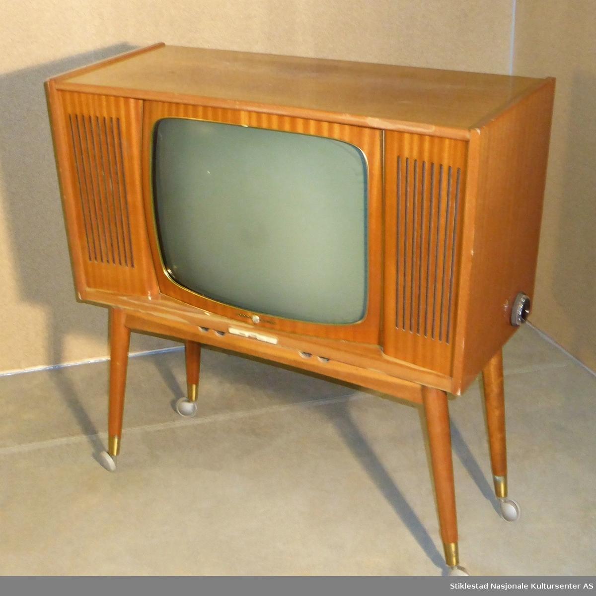 """Tv-apparat fra Tandberg av merket Radionett Grand TV kabinett. Lakkert trekabinett montert på løse bein med hjul som skal skrus fast til tvkasse. Messingholker i nedre del av bein. Stereo tv (høytalere på hver side) med buet skjerm. Messingkrans rundt tv-rute og skjerm.  Hvite betjeningsknapper i plast under skjerm, samt svart stillhjul i plast på høyre side.   """"Den mest etterspurte tv-modell, 23"""" stor billedrør, 2 store konserthøytaler"""" (reklame fra Tandberg 1961)."""