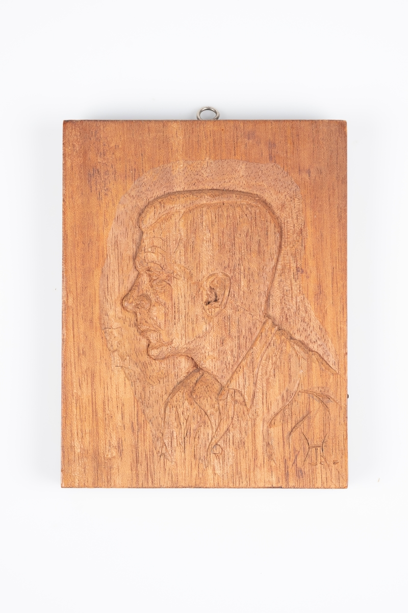 Et portrett i trerelieff. Den har en øyeskrue øverst for oppheng. Det er inngravert initialer i høyre hjørne på framsiden. På baksiden er det pålimt en lapp med informasjon om relieffet som trolig ble limt på i etterkant.
