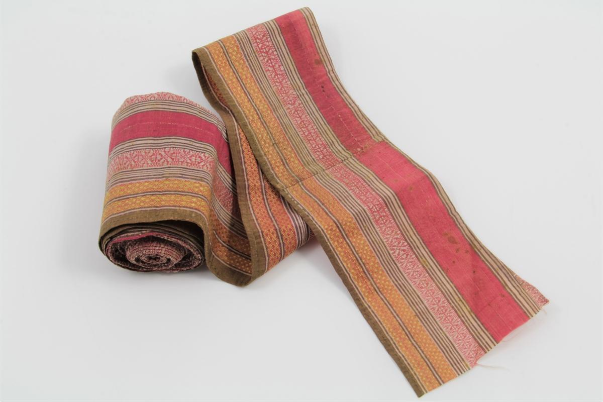 Bånd i vevet silke. Langsgående ensfargede striper i rødt, brunt og kremfarget, samt røde striper med mønster i hvitt eller gult. Toskaft og langsgående flotteringer.