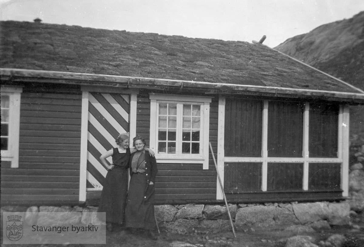 To kvinner utenfor hytte eller fjellstue