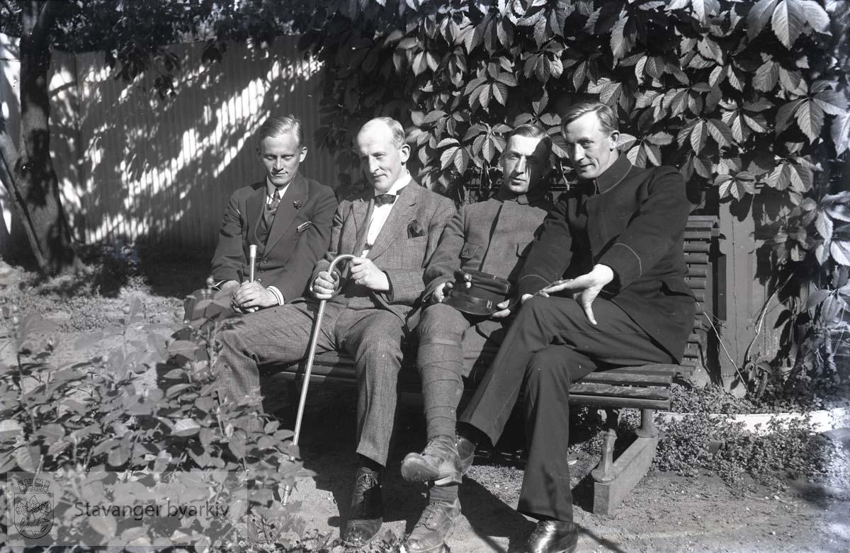 Fire menn på benk i park eller hage