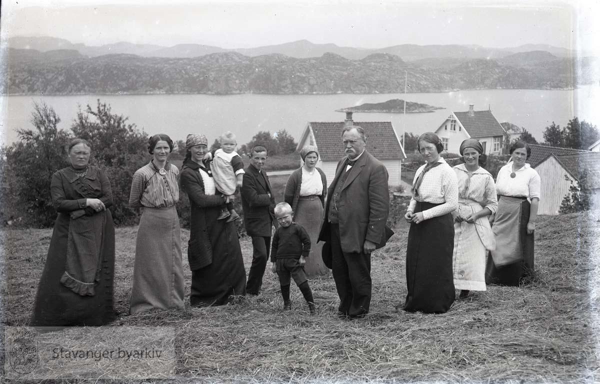 Familie på tunet foran våningshus
