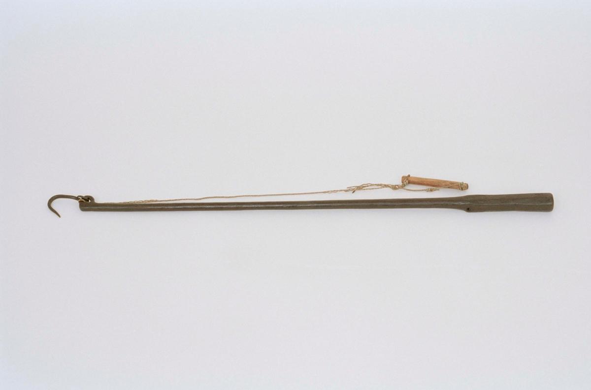 """Besman av järn, handtag av trä och snöre. Märkt på skaftet med 3 bomärken samt """"ANO 1640"""". Punsade markeringar."""