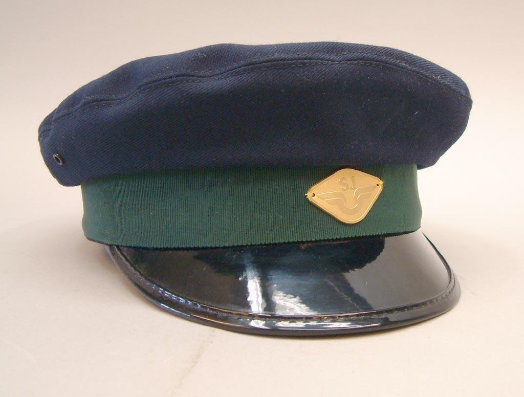 Mörkblå skärmmössa med högt vinterkapell. Mössan har grönt mössband och guldfärgat mössmärke med SJ-logga, men ingen mössträns. Storlek 55.