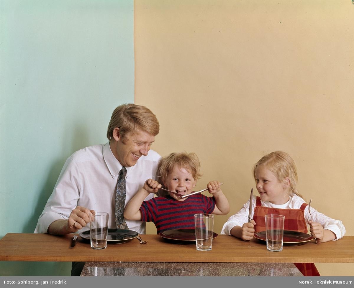 En mann og to barn, en gutt og en jente, sitter ved et bord.Foran seg har de tomme tallerkner og glass. Det ser ut som en liten familie som venter på middag.
