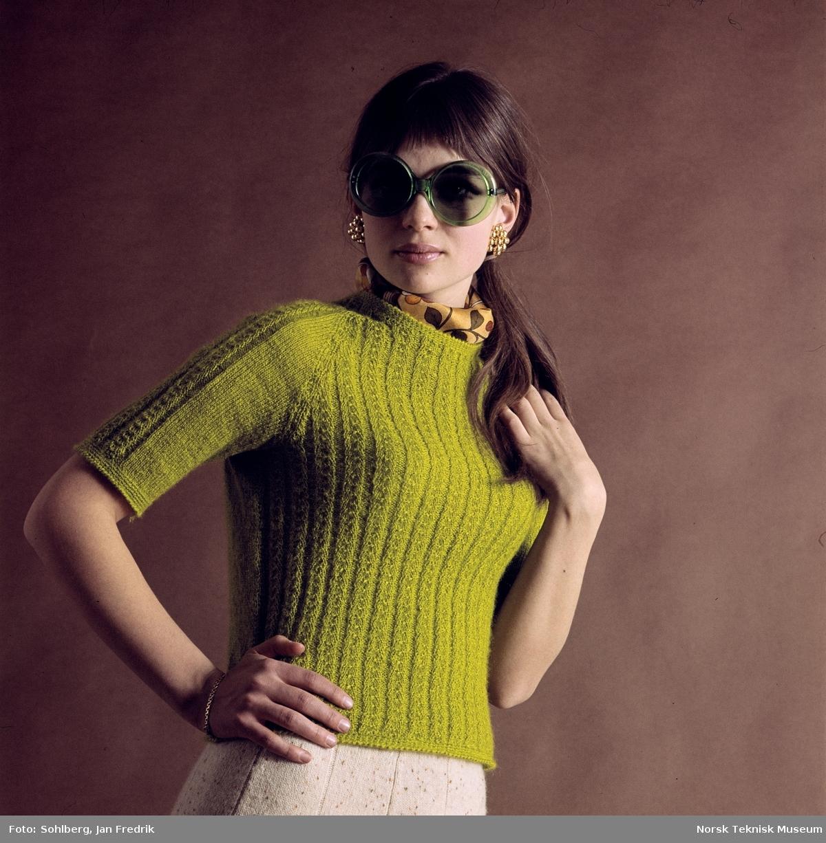 Kvinnelig modell med en grønn mønstret strikket topp med halvlange ermer.