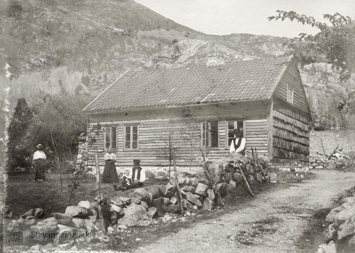 To menn og to kvinner foran hus i fjellet.