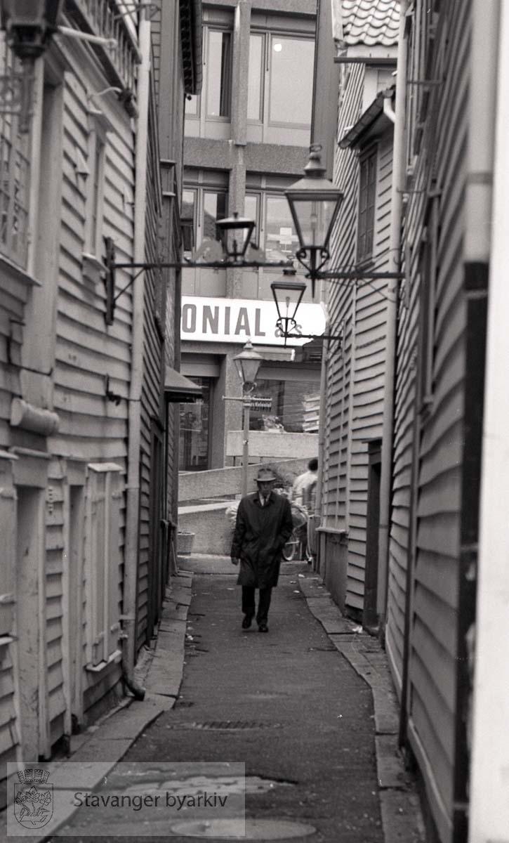 Mann med hatt.Litt av Torvets Kolonial i bakgrunnen