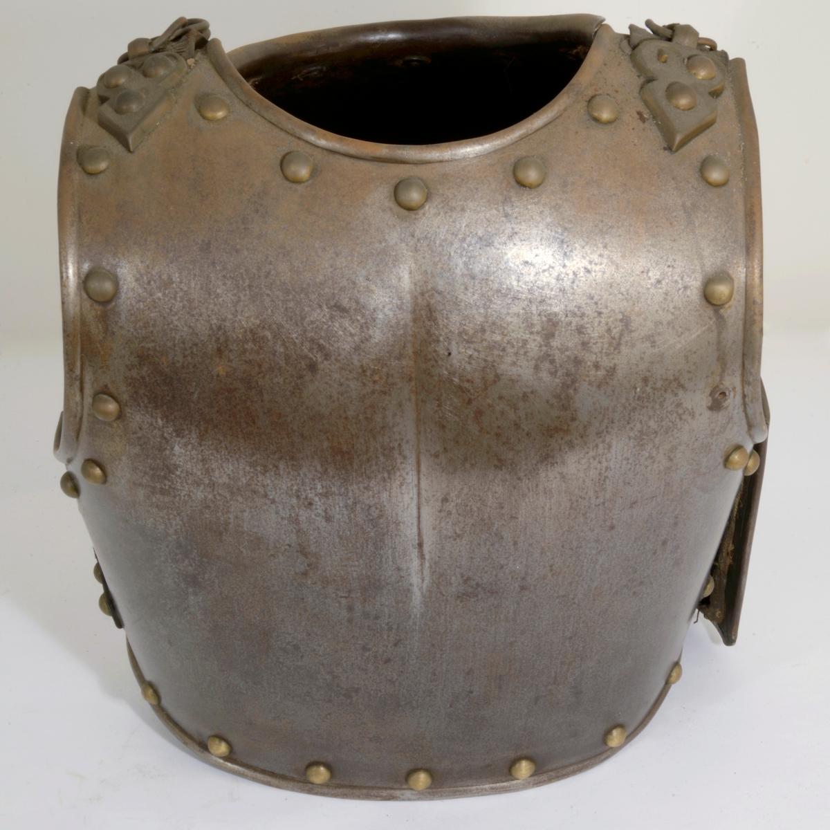 Kyrass bestående av brystplate på nr A.03241og ryggplate på nr A.03242. Platene er kantet med messing nitter. Lærremmer med jernringer er festet på ryggplaten og festet til nitter på fronten av brystplaten. Ryggplaten er foret med strie.