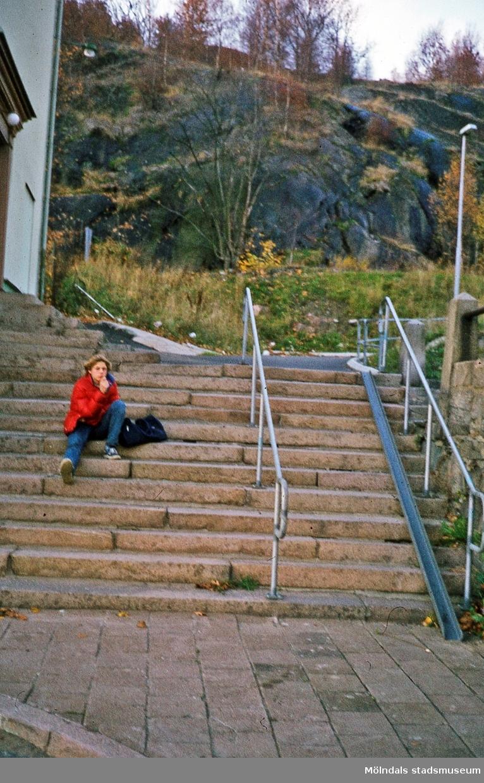 Vy från Gamla Torget i Mölndals Kvarnby mot trappan som leder till den gångväg som kallades Samuel Norbergsstigen. Okänt årtal. En pojke sitter i trappan. Till vänster ses liten del av gaveln till gamla stadshuset med adress Kvarnbygatan 43. OBS rännan för cykel.