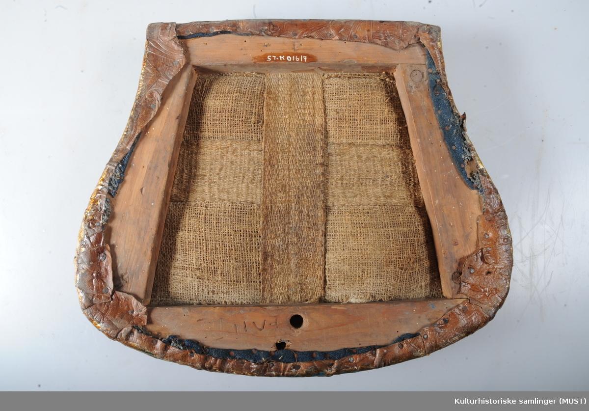 Stolen er av den almindelige rokokkotype.  Ryggen er åpen med et profilert brett som ender i en musling. Sargen har også et usymmetrisk muslingornament. Stolen er trukket med gyldenlær, blå bunn.