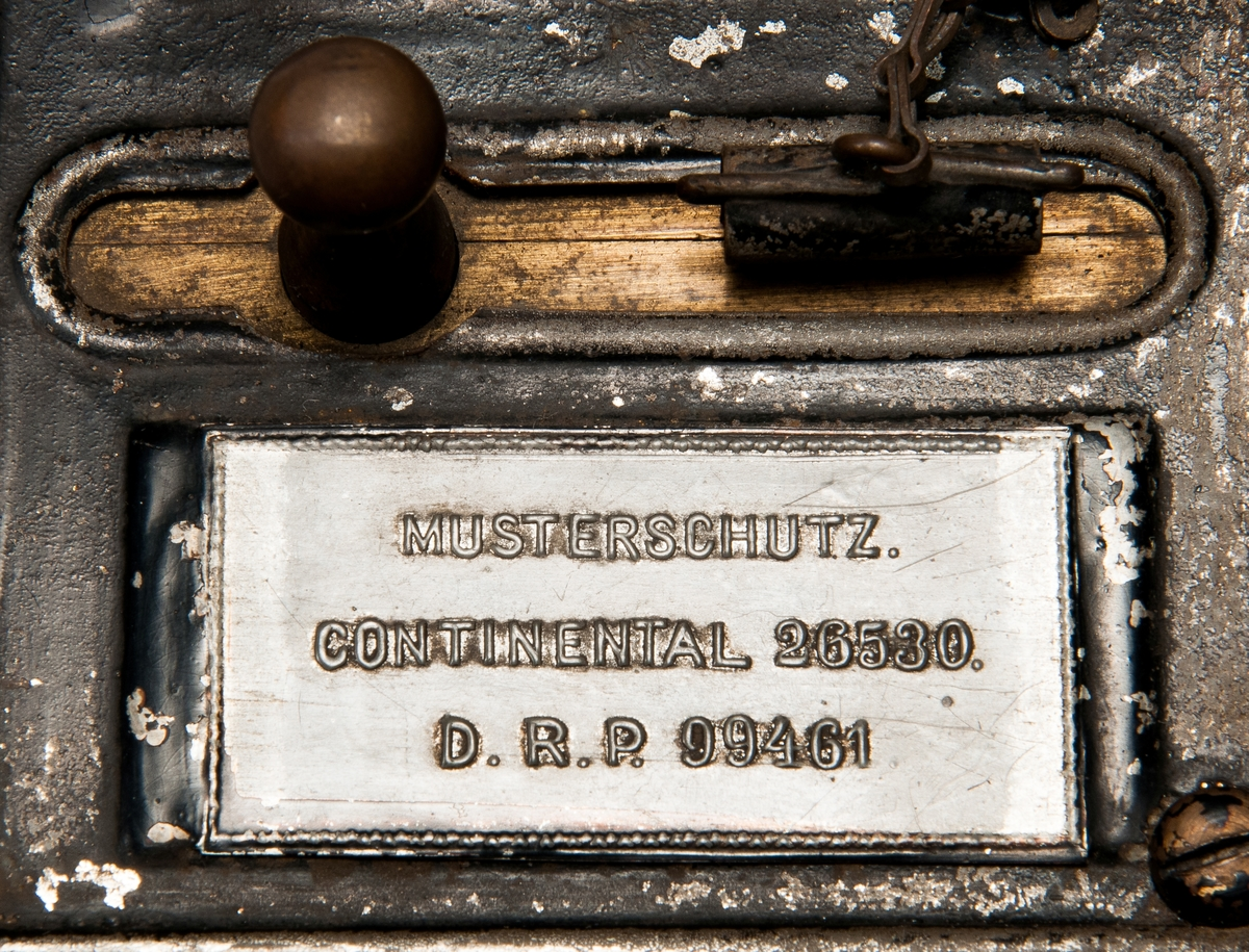 """Svart, fyrkantig gasmätare med tysk text. Har en lucka nära toppen och en stor """"1"""" målad i rött på sig. Har en stämpel under ettan. Stämpeln har texten: """"Deutsche Continental Gas Gesellschaft Dessau III Gasmesser für 5 flammen No 121344, 1905"""" på ovansidan finns liten skyllt med text: """" Musterschutz continental 26530 D.R.P. 99461"""". Polettlådan har ett hänglås ( nyckel saknas ) mätaren är påmålad 213."""