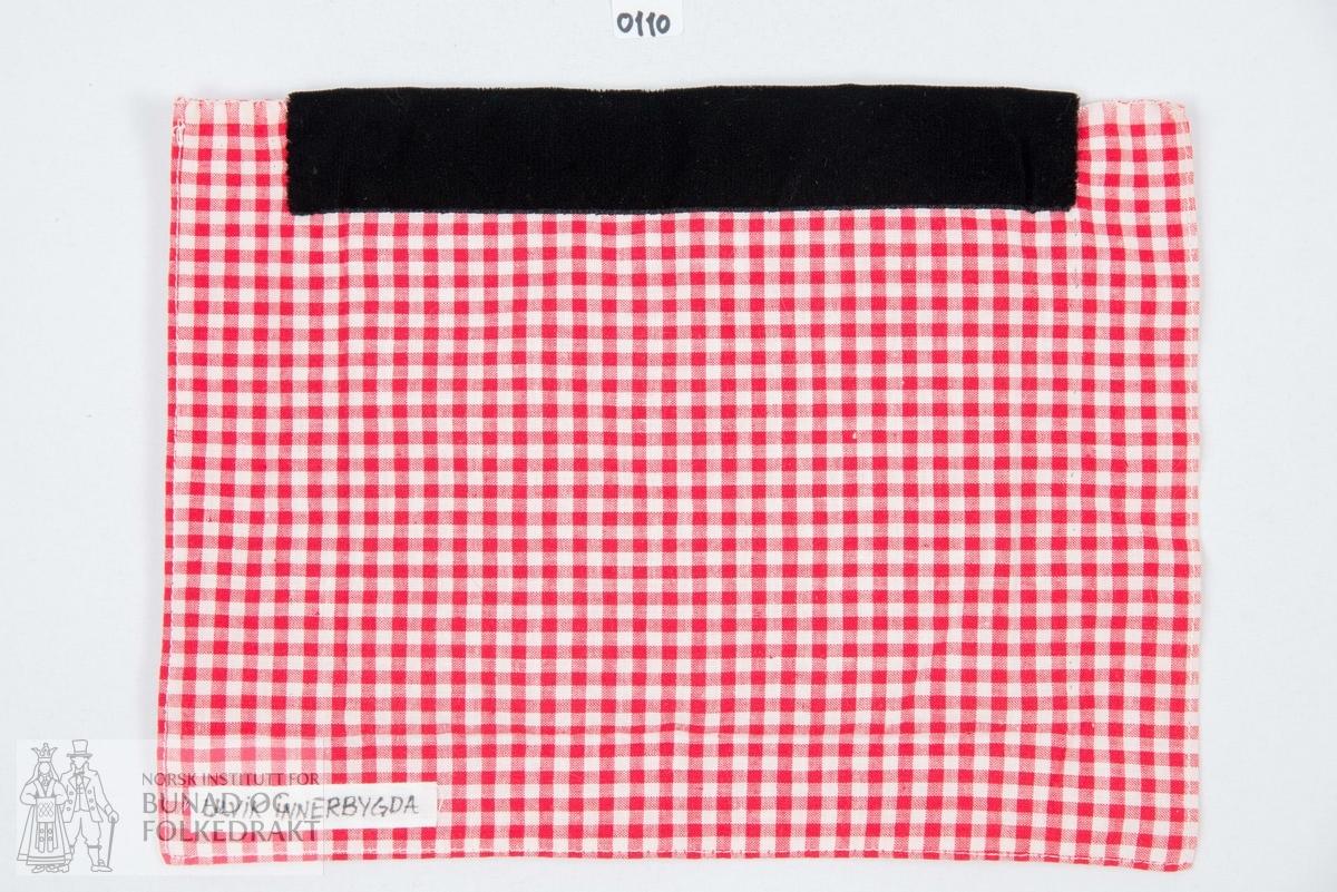 Bringeduk. Vevd bringeklut med åttebladroser i hvitt, svart, rødt, grønt og gult i ullgarn. Påsydd silkeband i lysegrønt og grønt, krokaband, på hver side. Øverst på bringekluten er det sydd på en kant med svart bomullsfløyel. Hele kluten er sydd til et stykke rød/hvit rutete bomullslerret. Maskinsydd.