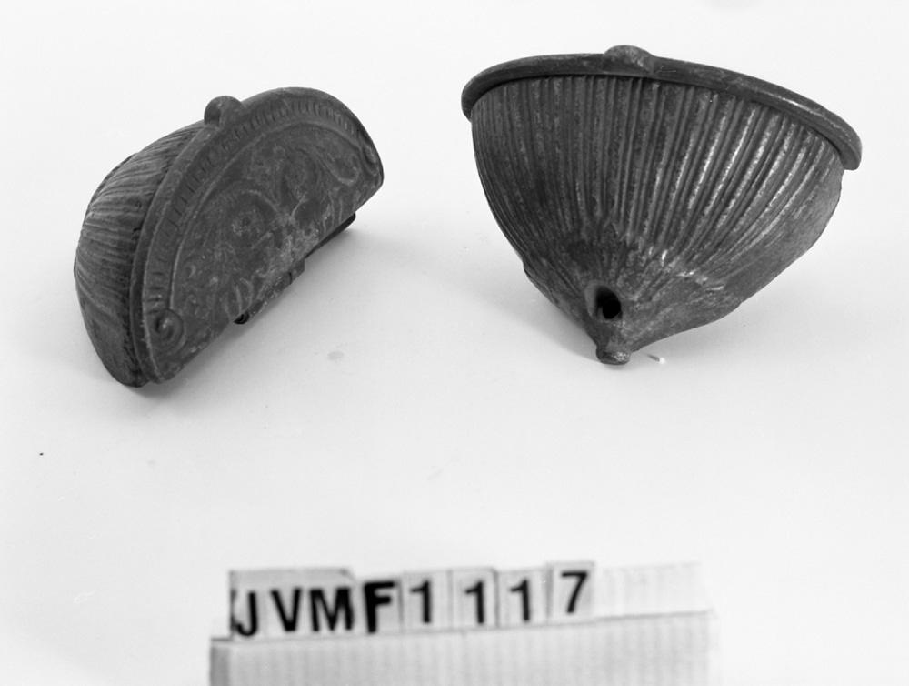 Två askkoppar i form av en halv oval, med räfflad kopp och lock med blomdekor. Troligen av gjutjärn, men numera brunfärgad.