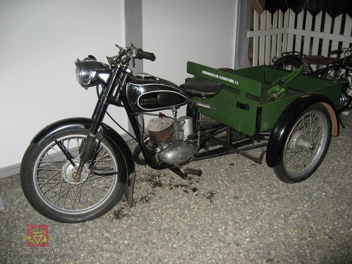 """Svart (RAL-9005 SORT). 3-hjuls motorsykkel med grønn varekasse. Motorsykkelen er utstyrt med ensylindret bensindrevet forbrenningsmotor, 123 ccm Sachs motor, type SM 55.  Fra Tempoklubben har vi hentet generell beskrivelse på Transport modellen: Kjennetegn: 1 hjul fremme og 2 bak med varekasse bak. Solid bakaksel av spesialstål. Laget med 4 kraftige kulelager (SKF6205). Spesialbygget differensial. Grønnmalt varekasse i tre. Innvendige mål: lengde 90cm, bredde 77,5 cm, høyde 23 cm.  Produksjonsperiode: 1958-1969. Produsert i Sandnes, Norge. Ramme: kraftig modell med forsterket styrehode. Bygget av stålrør. Alle forbindelser er sveiset elektrisk. Forgaffel: teleskopgaffel. Solid gaffellås på styrehodet. Felger/eker: lakkerte stålfelger. 3 mm eker. Dekk, slange: 2,75"""" x 19"""". Nav: trommelbremsenav av eget fabrikat. Bremser: 125 mm bremsetrommel. Skjermer: solide brede stålskermer. Kraftige skjermstivere. Styre: stillbart. Sal: stort behagelig svingsal med dobbelt gummidekke. Stillbar fjæring. Pedaler/fothvilere: fotholderrør med gummiblokker. Ekshaustanlegg: forkrommet ekhaustrør. Demonterbar lyddemper. Elektrisk utrustning: tennings- og lysbryter. Likeretter. Akkumulator (6 volt 8 Ah) for signalhorn, parkeringslys og stopplys. Signalhorn: elektrisk horn. Stopplyslampe: 6 v 15 w. Baklyslampe: 6 v 3 w. Forlyslampe: 6 v 25/25 w. Parkeringslampe: 6 v 1,5 w. Kraftoverføring/Drift/Kjede: kraftig motorsykkelkjede 1/2"""" x 1/4"""" med 8,5 mm ruller. Kjedestrammetrinse i kulelager (SKF 6205). Kjedekasse: åpen kjedeskjerm. Bensintank: lakkert ståltank. Kneputer. Rommer ca. 11 liter. Bensinkran med reservestilling. Drivstoffblanding: 1:25 (4%). Største lengde: 2370 mm. Største bredde: 1130 mm. Akselavstand: 1630 mm. Modellendringer: Transport med 100 ccm motor fikk navnet Transport 515. Motor: Sachs 150 (1958), Sachs 125 (1959-66), Sachs 100 (1967-69), 175 på bestilling."""
