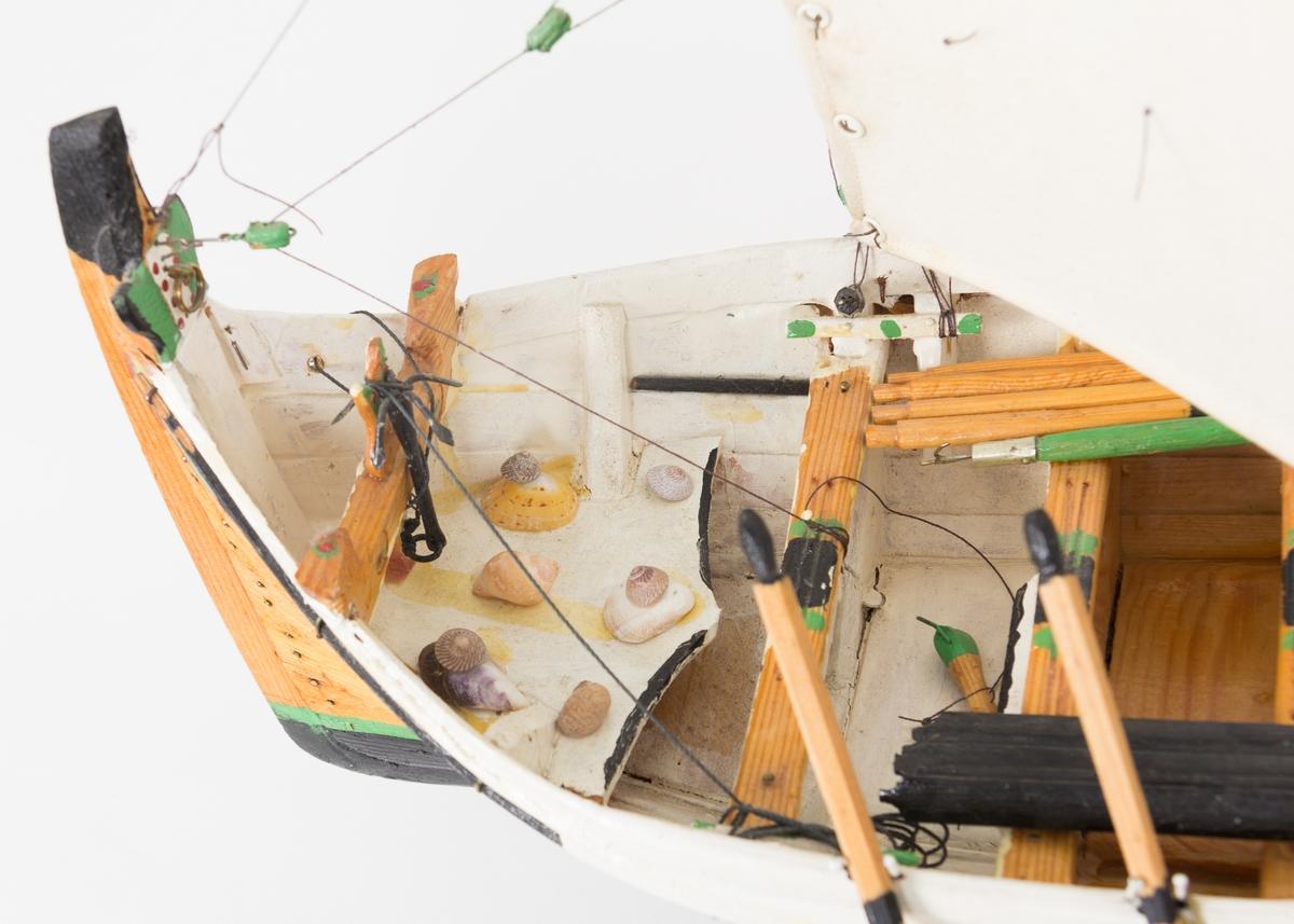 Modell av nordlandsbåt - en fembøring med syv årepar og fem par tollpinner, seks tofter og et øsekar og en båtshake. Båten har en løfting med pipe og dør og to ventiler i simsen og er rigget med råseil og toppseil. Ripa er malt rød, hvit, grønn, olivengrønn og sort. Kjølen og nederste delen av skroget er sortmalt (bunnstoff) med en smal grønn stripe øverst. Modellen står i en krybbe. I framskottet ligger det en dregg med fem klør. I tillegg har modellbyggeren limt fast 10 ulike skjell i framskottet. Ifølge informant ble denne typen dekor et trekk som kjennetegnet modellbyggerens båter etter hvert som han ble eldre.