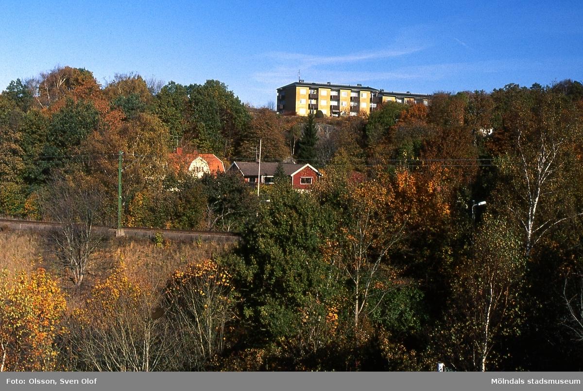 """Enerbacken i Mölndal, oktober 2003. Vy över järnvägen mot bostadsbebyggelse i """"Stusshålan"""" vid Kryssgatan. Uppe på höjden ses del av bostadshuset Lövgatan 1."""