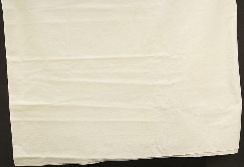 Hvitt bomullslaken. sydd sammen på langs av 2 bredder. en bred og ensmal fall på kortsidene