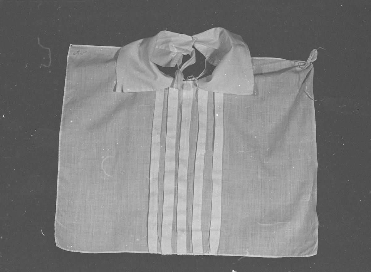 Fem biser foldet over til hver side fra midten av bryststykket.. Knytebånd festet nederst på hver snipp bak. Snipper festet til bryst 7,5 cm fra front.