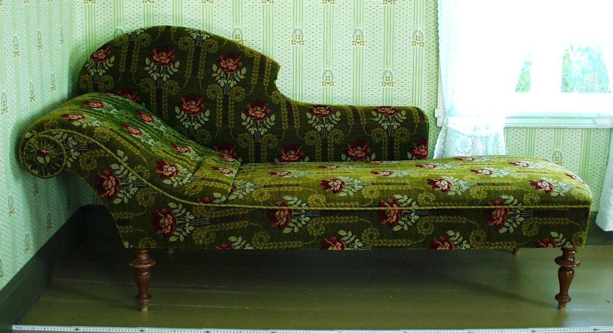 Sjeselong. Trukket i vevd, grønt stoff. Dekorert med store røde og lysegrønne blomster og blader. En snurret pyntesnor følger sitteflaten. Sitteplaten avrundes i en svull under hodeleiet. Dreide ben.