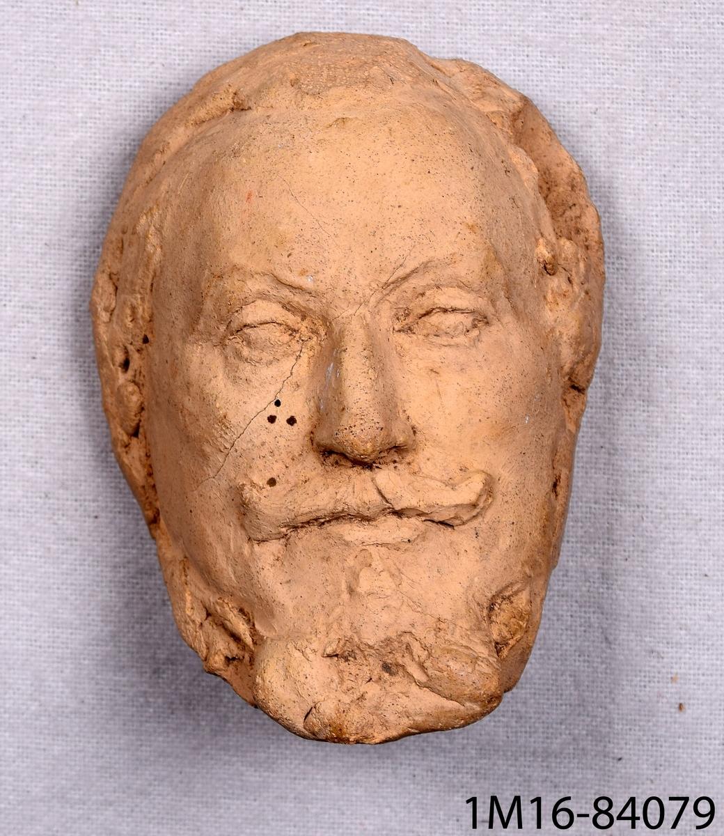 Modellerat ansikte av bränd lera, porträttet föreställer Axel Oxenstierna. Tillverkat av Hans Hagberg, Lidköping.