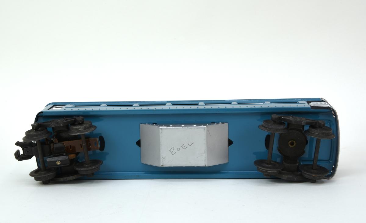 """Personvagn av plåt med boggier och elektromagnetisk vagnkoppling (:9). Vagnen är blå med tak, dörrar och fönster i silver. Fönstren är täckta med en lätt frostad plastremsa och vagnen saknar inredning. På sidorna under fönsterraderna finns """"2431"""" och """"OBSERVATION"""" tryckt i silver. Taket är fäst med en skruvad klammer i korgen som är pressad ur ett plåtstycke. Boggierna är vridbara och den ena har en liten strömupptagare för att aktivera den elektromagnetiska vagnkopplingen. I vagnens bakända finns en öppen plattform med galler i silverfärgad plåt och två baklysen (utan lampor) placerade i de övre hörnen. Inne i vagnen finns en glödlampa som dock inte är inkopplad då vagnen saknar strömupptagare och ledning till lampan.  Till vagnen hör en förvaringsask i kartong (:10) med tillverkarnamn och modellnummer tryckt i blått mot orange botten."""