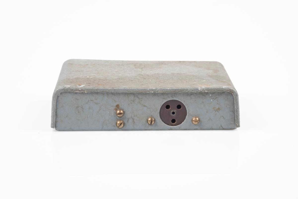 Tørrbatteri til kortbølgeradio med ytterplater er av metall som er lakkert i grått. På baksiden er det kontakt med 3 hull til kobling av ledning på radio.