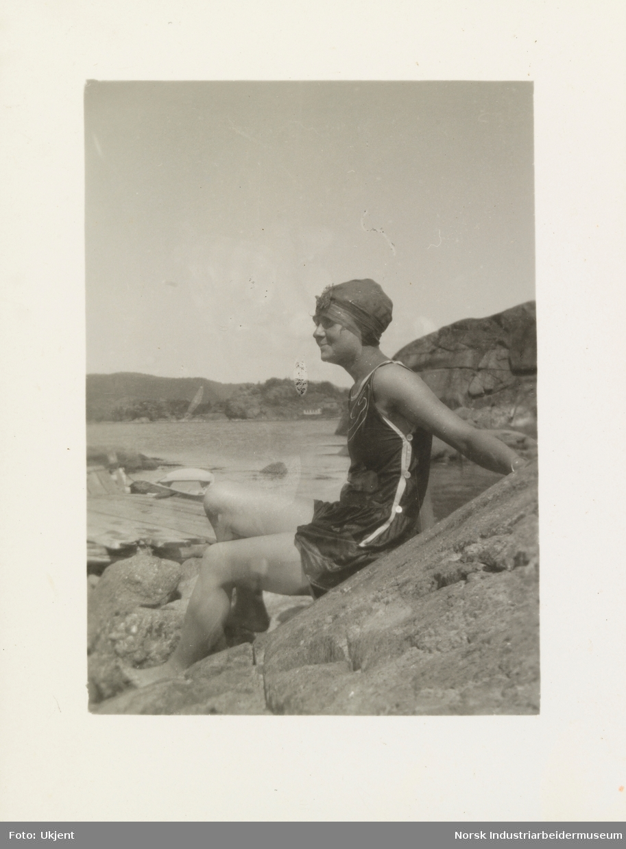 Kvinne i badrakt og lue sitter på svaberg etter et bad i sjøen