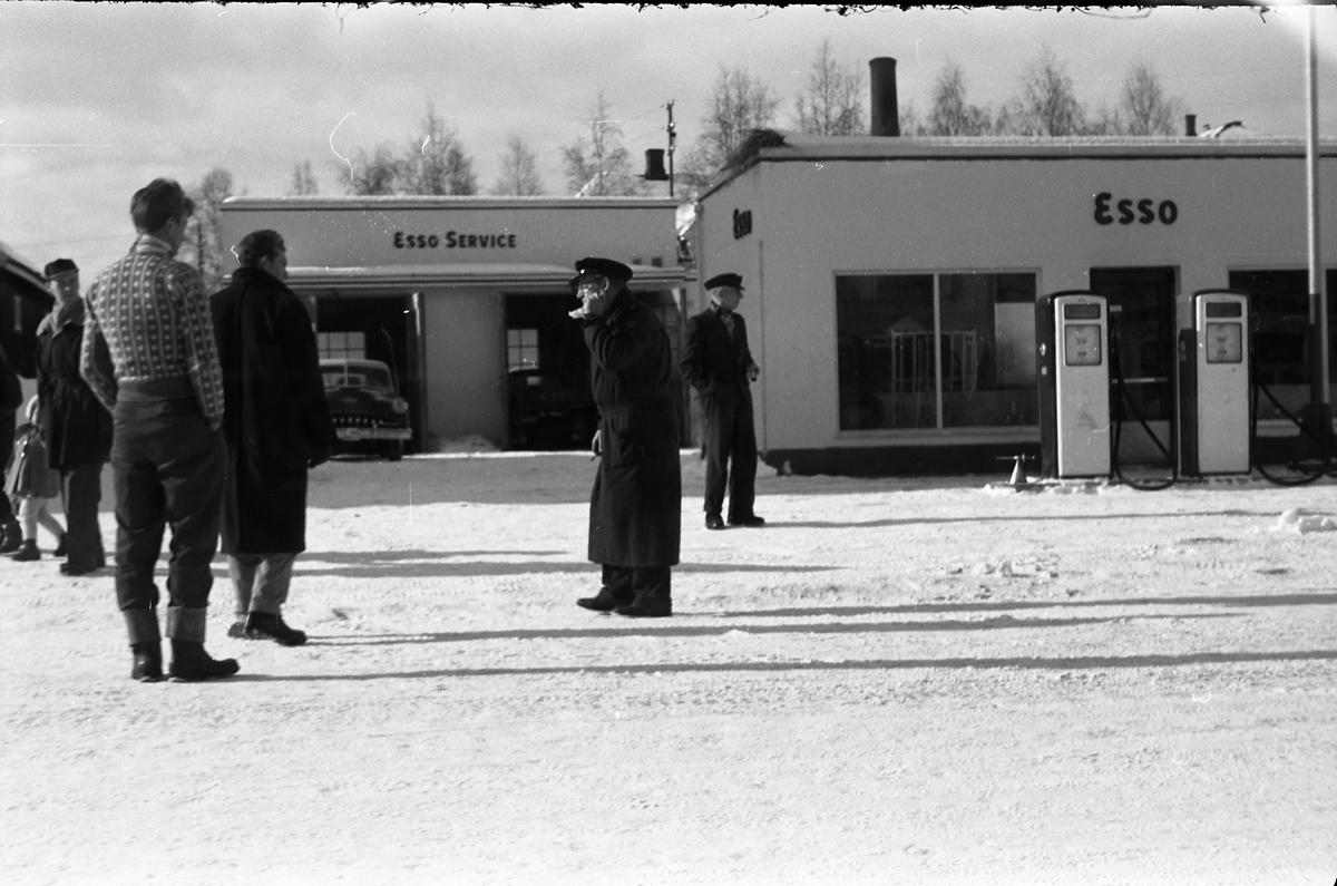 Tre bilder av noen mannfolk ved Esso benstinstasjonen på Lena februar 1958. Helt til høyre på alle tre bildene er muligens Torbrjørn Lundsten, drosjesjåfør fra Kraby, og til høyre for han muligens Paul Grindvoll. Bilen i bakgrunnen er iflg. informant en drosjeregistrert De Soto årsm. 1951-53.