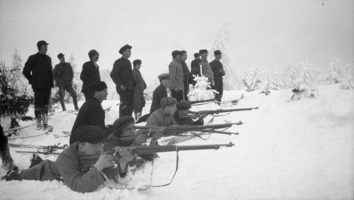 Tre skiskyttere i aksjon, mange tilskuere