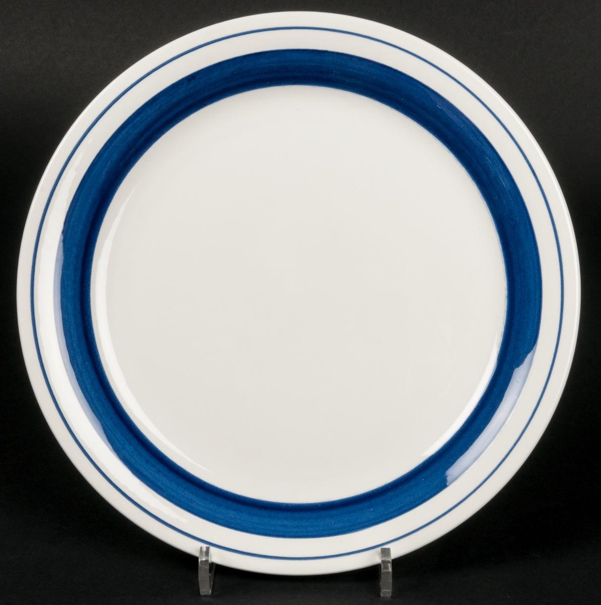 Tallrik. Vit med blå dekor i raka band runt kanterna. VDN-märkt F555. Dekor: Marin